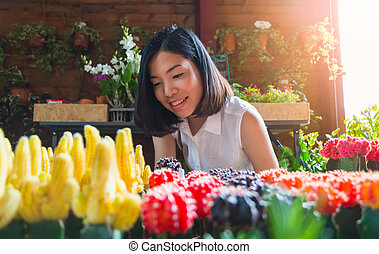 an asian young woman is looking at the small cactus