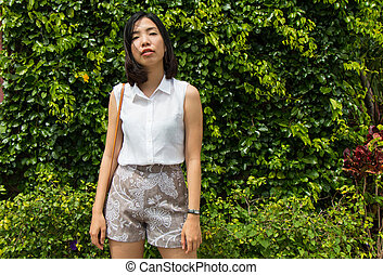 an asian young woman is standing
