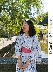 an asian young woman smiling and wearing Yukata