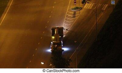 An asphalt washing machine rides on the road. Mid shot