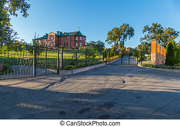 An asphalted playground in front of the gate leading to a beautiful two-story brick house standing on a hill with a beautiful garden in the yard.