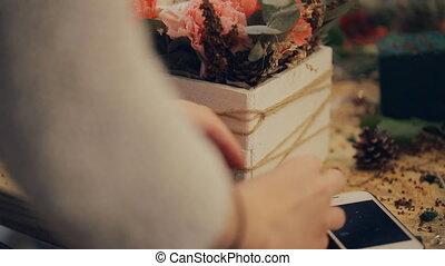 an aspiring florist uncertainly lays fir cones on a pot with...