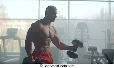 An athlete On the background of a window with a beautiful body lifts weights to train your biceps in the gym. Strength training to build muscle. Hard and hard training for strong hands.