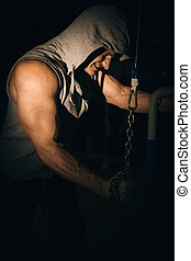 an athlete pumps his arm muscles with a chain in the gym on a dark background,