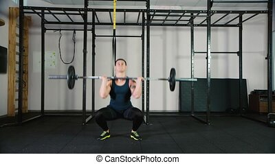 An athlete trains with a barbell