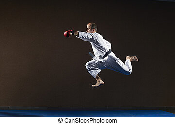 An athlete with red overlays on his hands beats a blow with his hand in a jump