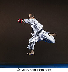 An athlete with red overlays on his hands trains a punch with his hand in a jump