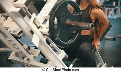 An athlete woman training in the gym - sitting down on the training apparatus. Mid shot