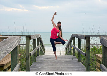 an athletic brown haired woman is doing yoga exercise dancing shiva tree pose on an empty boardwalk at the gulf of mexico in naples florida at sunset