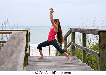 an athletic brown haired woman is doing yoga exercise warrior 1 pose on boardwalk at beach in the gulf of mexico in naples florida at sunset.