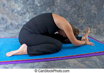 An athletic brown haired woman is doing yoga exercise  Knee to the Head  pose or Janu Sirsasana posture on yoga mat in studio with mottled background.