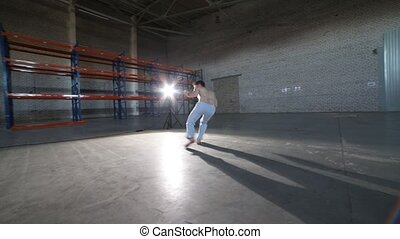 An athletic man doing difficult capoeira elements in the room with concrete floor and brick walls - Mid shot