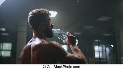 an athletic man drinks vodka to restore strength after and before performing an exercise in the gym. drink water from a bottle during your workout. High quality 4k footage