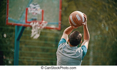 An athletic man jump and about to throw the ball in the basketball hoop