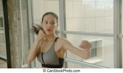 An athletic woman boxer taking a deep breath and boxing and...