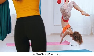 An athletic woman hanging upside down in hammock for yoga ...