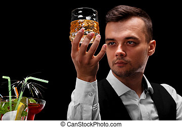 An attractive bartender holds a glass of whiskey, margarita glasses on a bar counter on a black background.