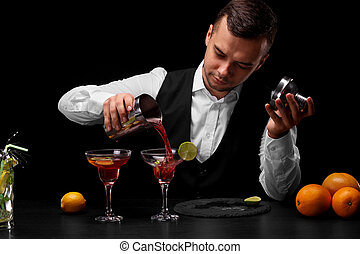 An attractive bartender pours a cocktail in a margarita glass, oranges, lemon, slices of lime on a black background.