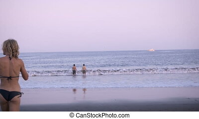 An attractive blond woman runs into the ocean while two men...