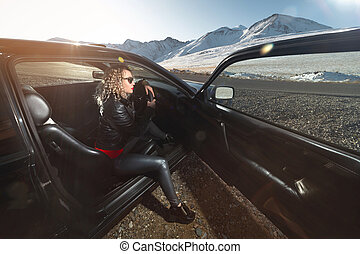 An attractive blonde in sunglasses and leather clothes sits in a black leather salon with an open door of a sports car on a country road in the mountains at sunset. Retro style 90s