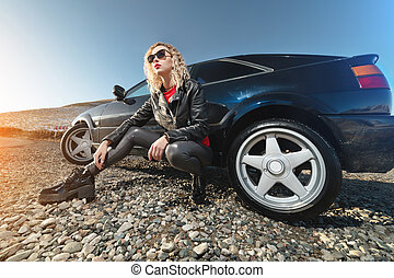 An attractive blonde in sunglasses and leather clothes sits near a black sports car on a country road in the mountains at sunset. Retro style 90s