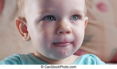 An attractive boy 2 years old eats a red beet salad. The face is smeared with porridge. Sits on the table. Close-up