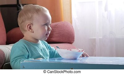 An attractive boy 2 years old eats a red beet salad. The face is smeared with porridge. Sits on the table.