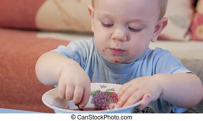 An attractive boy 2 years old is eating red soup himself....