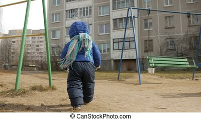 An attractive boy has been walking with his mother for 2 years in the playground in early spring. Dressed in a blue jacket and hat.