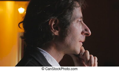 An attractive business man in deep thought turns to reveal...