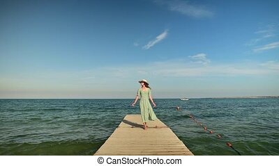 An attractive Caucasian girl in a green summer dress and a straw hat walks along the wooden pier of the sea coast in sunny weather. Rest at the sea. Travel video.