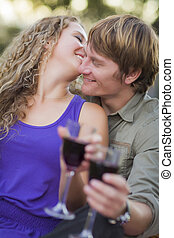 An Attractive Couple Enjoying A Glass Of Wine in the Park