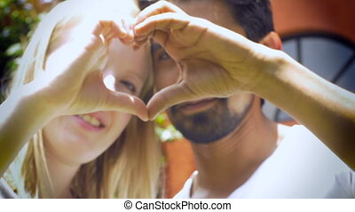 An attractive couple in love smile and make a heart with their hands