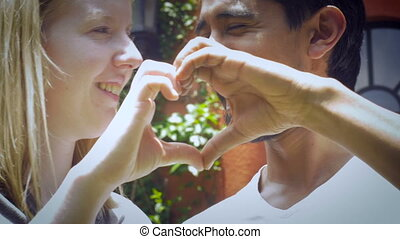 An attractive couple in their 20's in love make a heart with their hands