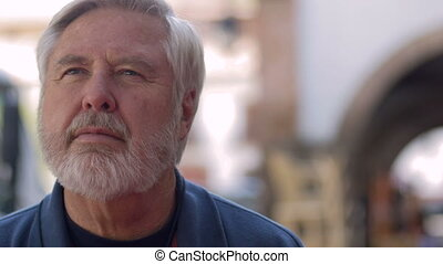 An attractive elderly man listening or concentrating on something outside