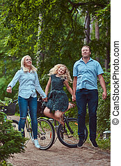 An attractive family dressed in casual clothes on a bicycle ride, have fun and jumping in a park.