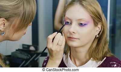 An attractive girl doing makeup