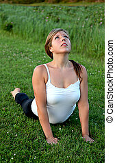 An attractive girl in a pose of yoga outdoors