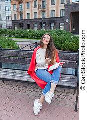 An attractive girl sits on a bench and writes her thoughts on the urban background in a red notebook. She wears a white sweater, blue jeans and a red plaid. A woman is thinking over an idea
