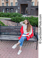 An attractive girl sits on a bench and writes her thoughts on the urban background in a red notebook. She wears a white sweater, blue jeans and a red plaid. A woman is thinking over an idea.