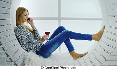 An attractive girl talking on the phone and drinking wine