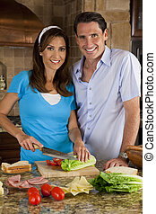 An attractive happy, smiling man and woman married couple making a healthy sandwich with ham cheese and fresh salad in a modern kitchen