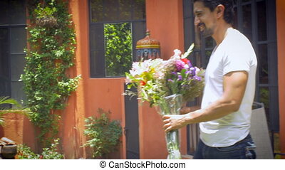 An attractive hispanic man brings flowers to a young blond woman wide shot