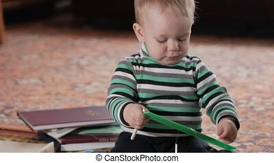 An attractive kid plays at home with a plastic ruler. He holds a pen in his hands. The boy is one year old.