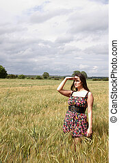 An attractive lady standing  in a corn field