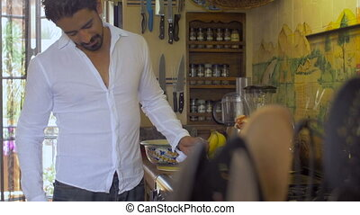 An attractive latino man cooks breakfast in a white linen shirt dolly shot