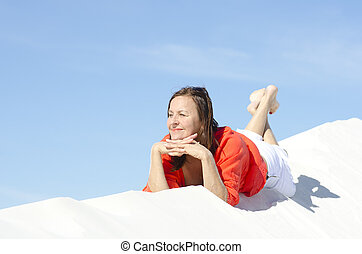 An attractive looking middle aged woman, wearing abright red blouse, is lying relaxed and happy on top of a white sand dune, with blue summer sky as background and copy space.