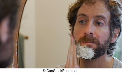 An attractive man with a full beard applies shaving cream to...