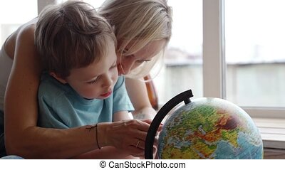 An attractive mother of caucasian ethnicity uses a globe to...