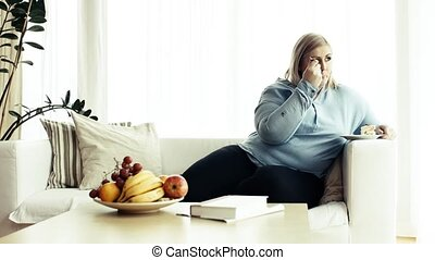 An attractive overweight woman at home, eating cake.